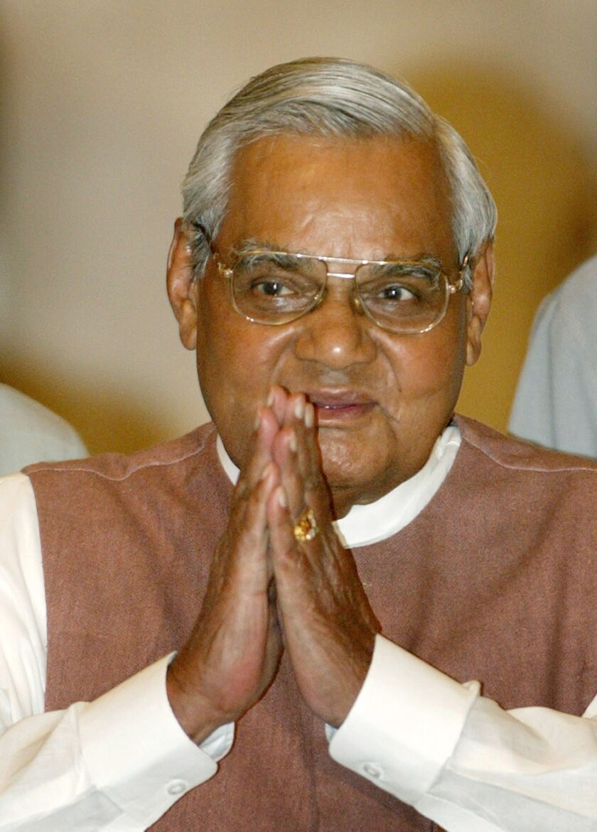 Indian Prime Minister Atal Bihari Vajpayee greets the audience as he arrives for a ceremony at the presidential palace in New Delhi on May 2, 2004.