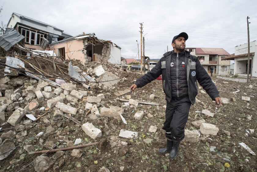 A man stands near the rubble of a house destroyed by shelling