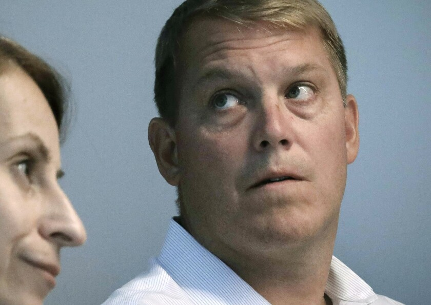 FILE - In this Aug. 20, 2019 file photo, Scott Hapgood, right, a U.S. financial adviser charged with killing a hotel worker while on vacation in Anguilla, and his lawyer Juliya Arbisman, left, hold a media conference in New York. Hapgood declined to return to the British Caribbean territory for the latest pretrial hearing on Monday, Nov. 11, and Anguilla officials rejected an offer that he appear by video link for the hearing. (AP Photo/Bebeto Matthews, File)