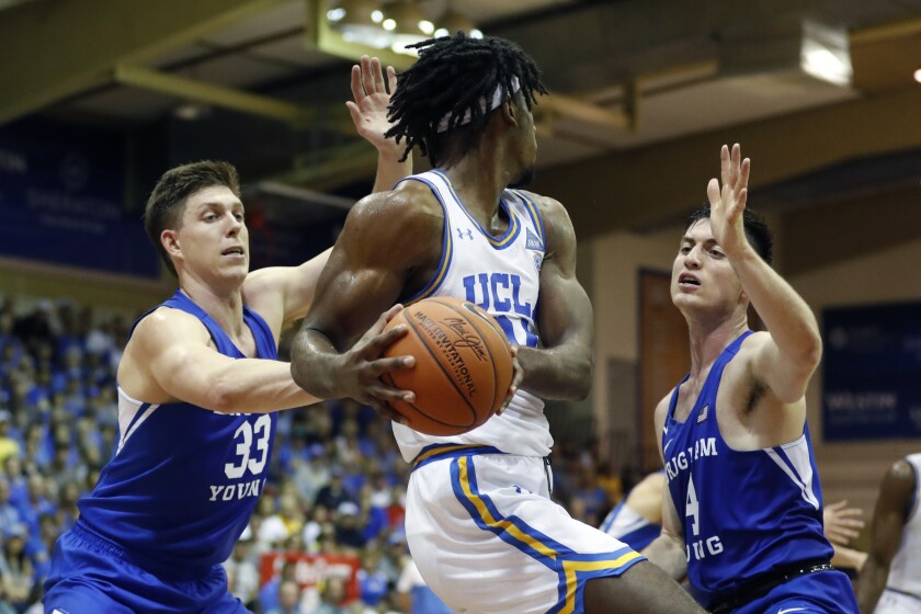 UCLA forward Jalen Hill (24) is double teamed by BYU forward Dalton Nixon (33) and guard Alex Barcello (4) during a game Nov. 25 in Lahaina, Hawaii.