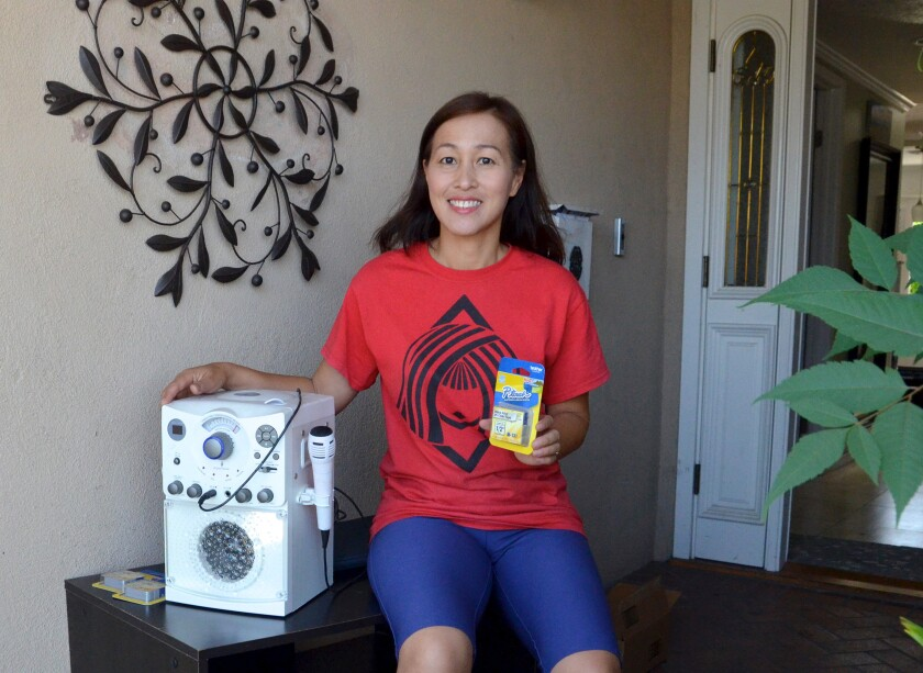 Costa Mesa Buy Nothing member Tho Tran Trefz is donating a karaoke machine, TV stand and print cassettes.