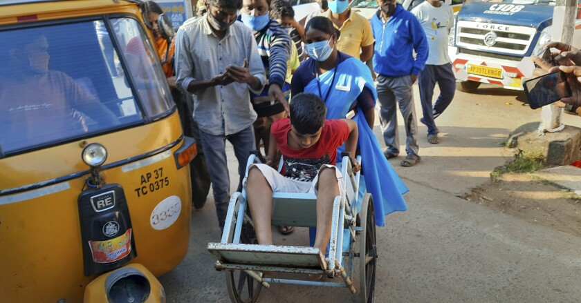 A young patient is brought in a wheelchair to the district government hospital in Eluru, Andhra Pradesh state, India.