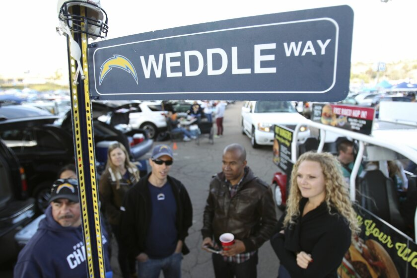Eric Weddle fans stand around a sign that has been put up every home game for nine years in the H-3 section of the parking lot.