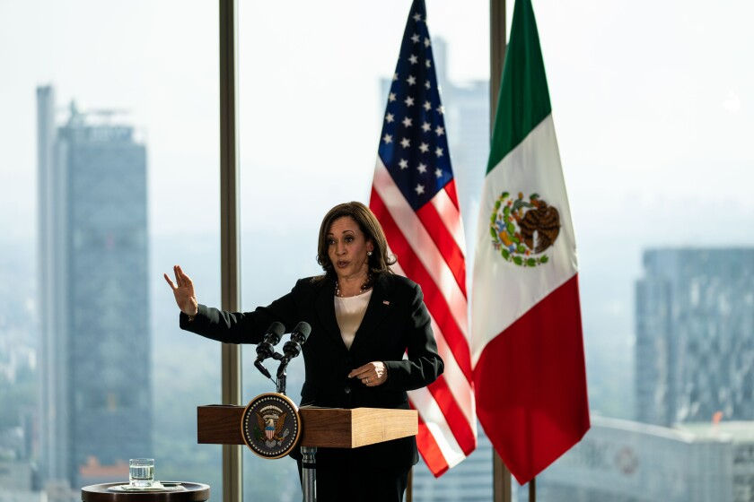 Vice President Kamala Harris in front of U.S. and Mexican flags