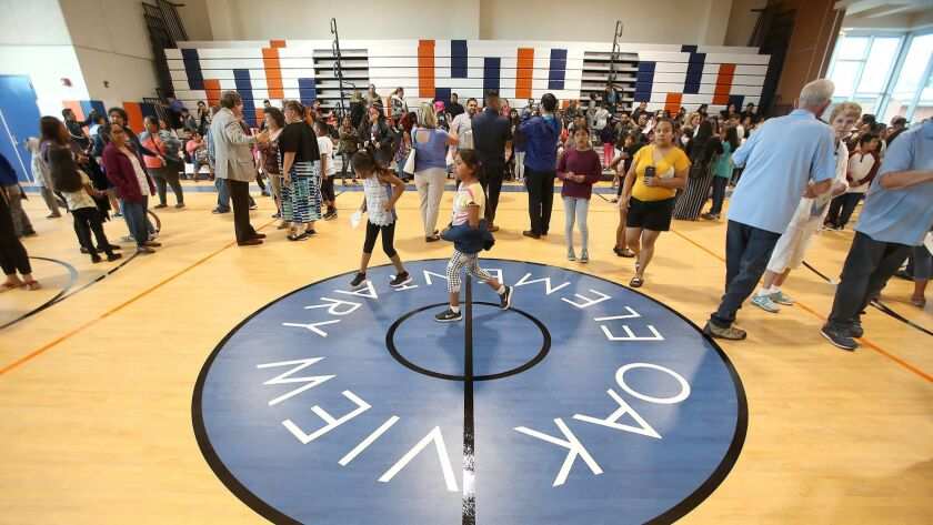 The center logo at the Oak View Elementary School gym and multipurpose room is unveiled during Monday's grand opening in Huntington Beach.