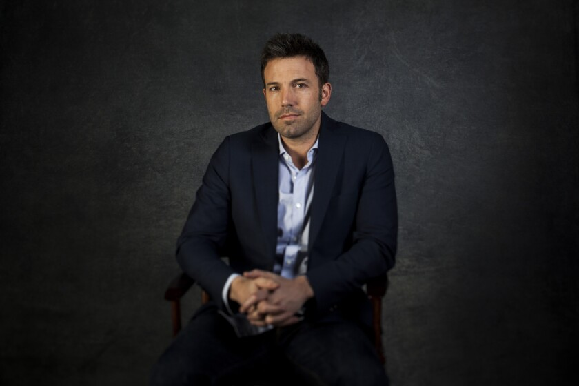 Ben Affleck poses for a portrait, seated with his hands clasped in front of a dark gray background