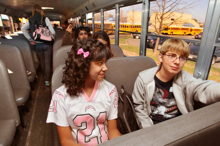Lorena Sanchez and Tom Paulus share a seat at the front of the school bus for their ride home from Olive Peirce Middle School in Ramona on Thursday, hours after state lawmakers approved funding to keep school buses rolling across California.