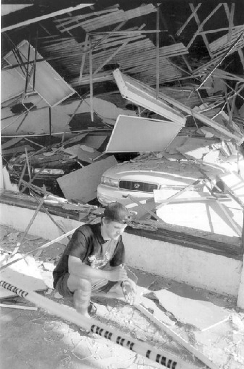 David Lane checks damage in front of a Mazda dealership in Santa Monica after the 1994 Northridge earthquake. Santa Monica adopted regulations on retrofitting vulnerable buildings, but its resolve has faded in recent years.