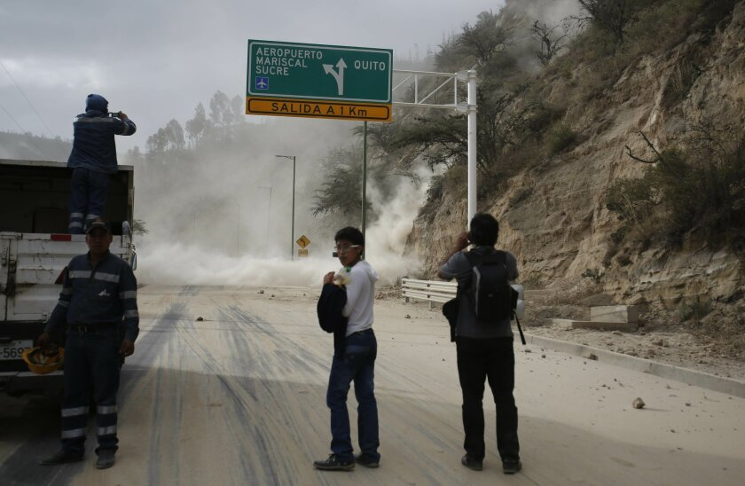People watch as earth and dust spill on the Pan-American highway as result of an earthquake, at Oyacoto, north of Quito, Ecuador, Tuesday Aug. 12, 2014. A magnitude-5.1 earthquake shook Ecuador's capital and surrounding areas Tuesday, causing tall buildings to sway and sending some people rushing into the streets. (AP Photo/Dolores Ochoa)