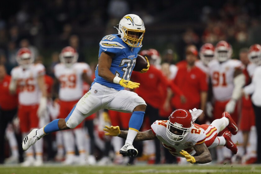 FILE - In this Nov. 18, 2019, file photo, Los Angeles Chargers running back Austin Ekeler, left, gets past Kansas City Chiefs strong safety Jordan Lucas, right, during the first half of an NFL football game in Mexico City. Ekeler's breakout season with the Los Angeles Chargers has resulted in a contract extension. The running back has agreed to a four-year deal with the Chargers worth #24.5 million, including $15 million guaranteed. Ekeler was slated to be a restricted free agent when the new league year starts on March 18.(AP Photo/Eduardo Verdugo, File)