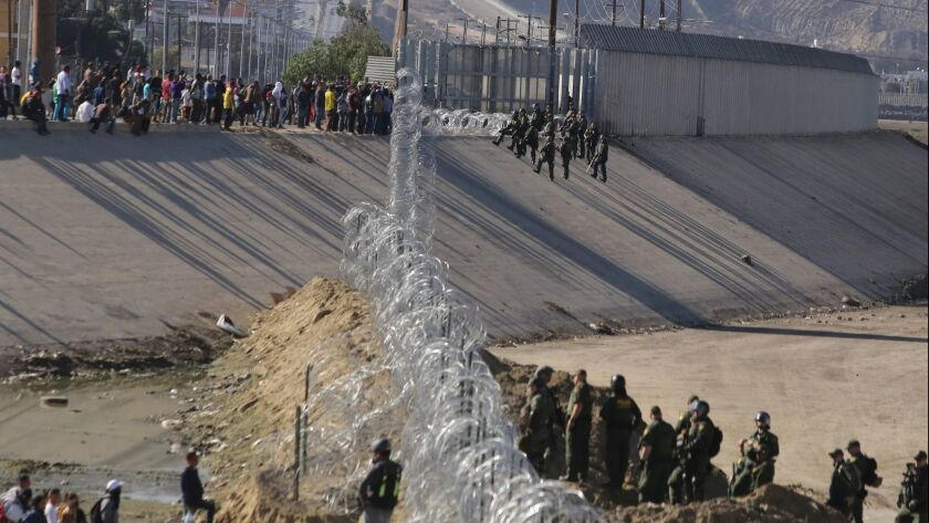Border police try to prevent groups of people from crossing the border from Tijuana, Mexico, on Nov. 25.