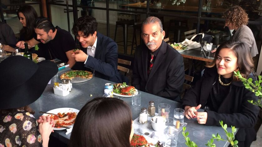 Artist Harry Gamboa Jr., center, sits with collaborators from his latest fotonovela in downtown Los Angeles.