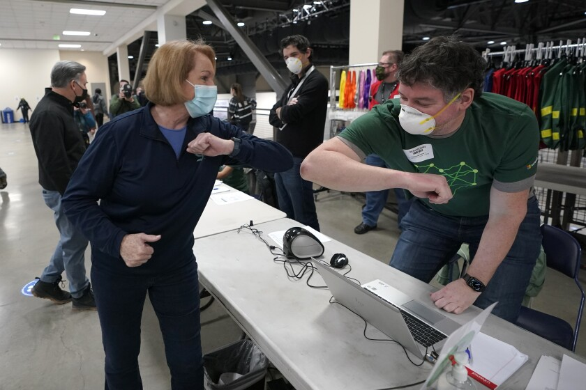 FILE - In this March 13, 2021, file photo, Seattle Mayor Jenny Durkan, left, greets a worker at a volunteer check-in station, on the first day of operations at a mass COVID-19 vaccination site at the Lumen Field Events Center in Seattle, which adjoins the field where the NFL football Seattle Seahawks and the MLS soccer Seattle Sounders play their games. Durkan said Wednesday, June 9, 2021, that 70% of city residents ages 12 and up have been fully vaccinated. (AP Photo/Ted S. Warren, File)