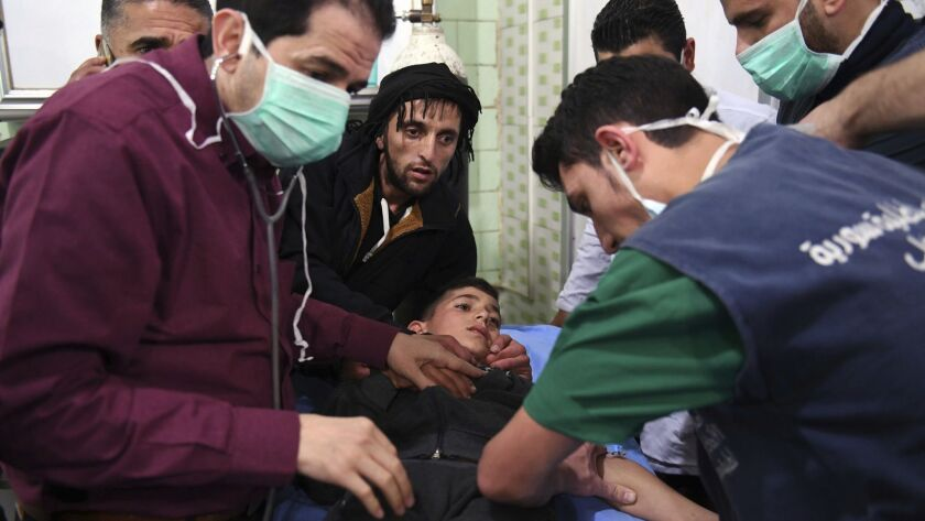 In this photo released by the Syrian official news agency SANA, shows medical staff treating a boy f