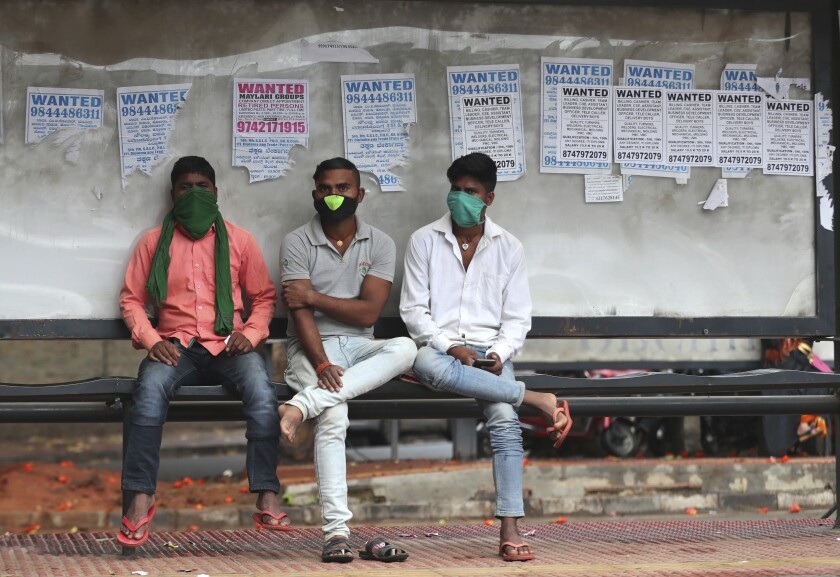 Indians wearing face masks as a precaution against the coronavirus wait at a bus stop in Bengaluru, India, Sunday, Oct. 11, 2020. India's confirmed coronavirus toll crossed 7 million on Sunday with a number of new cases dipping in recent weeks, even as health experts warn of mask and distancing fatigue setting in. (AP Photo/Aijaz Rahi)