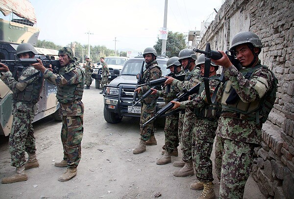 Afghan soldiers take position at the scene after several armed Taliban militants launched attacks in Kabul. Several Taliban suicide bombers were reportedly holed up in a multi-story building near several foreign embassies and NATO's International Security Assistance Force headquarters.