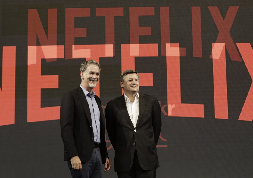 Reed Hastings and Ted Sarandos pose in front of the Netflix logo.