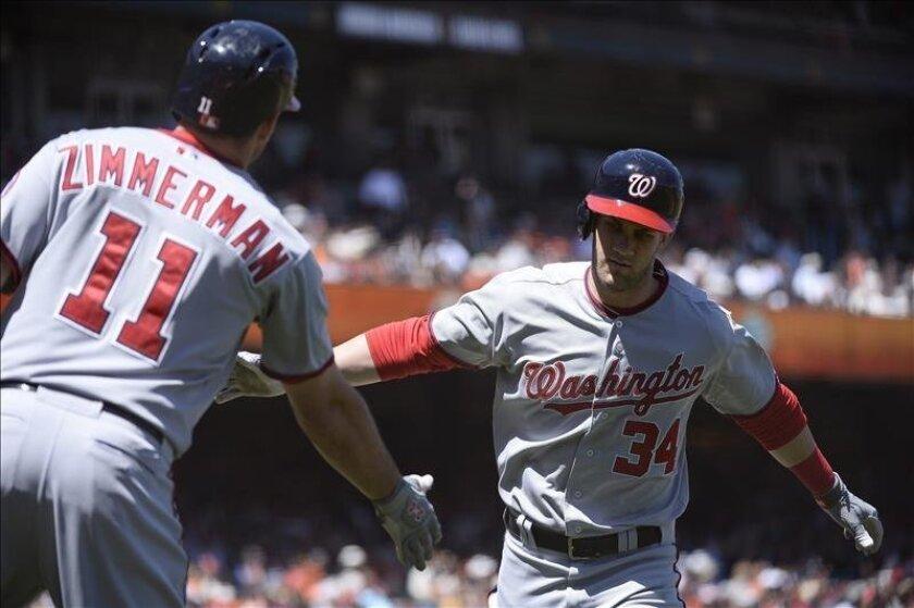 El jugador de los Nacionales de Washington Bryce Harper (d) es felicitado por su compañero Ryan Zimmerman (i). EFE/Archivo