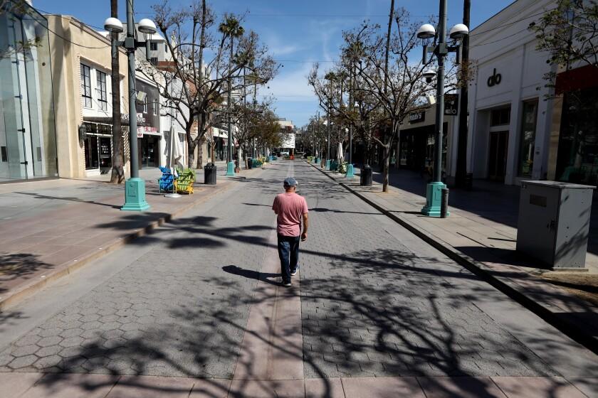 Kay Kabir, walks down a deserted Third Street Promenade in Santa Monica.
