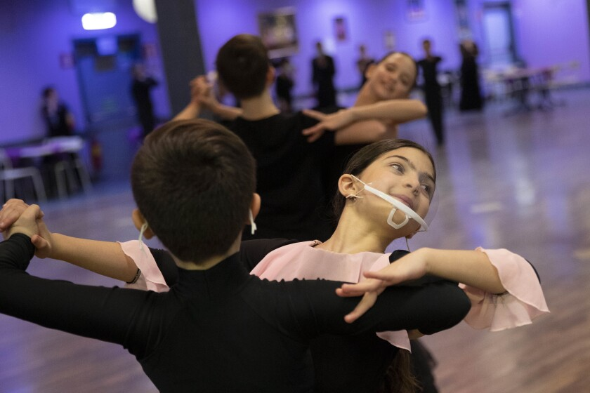 Young dancers, wearing face masks to curb the spread of COVID-19 train at the New Dancing Days school, in Rome, Wednesday March 24, 2021. While much of Italy is in coronavirus lockdown, with live music and theatrical performances barred, cinemas shuttered and many sporting activities limited, competitive ballroom dancing is alive and well here, albeit with precautions. (AP Photo/Alessandra Tarantino)