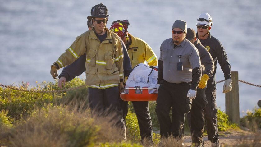 SAN DIEGO, CA 3/9/2019: San Diego Fire-Rescue Department personnel, assisted by others, carry the bo