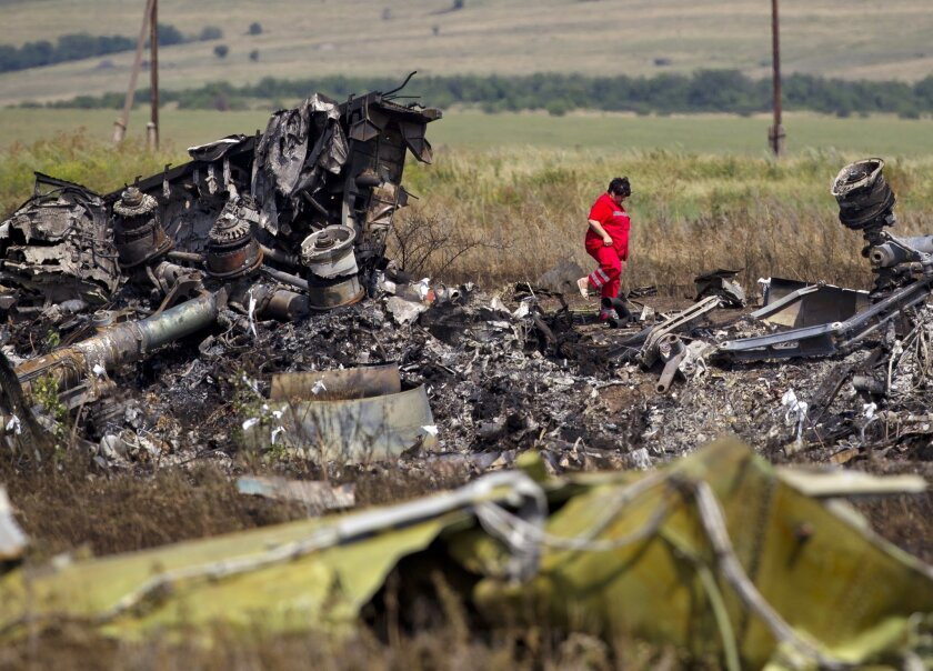 "FILE - In this Sunday, July 20, 2014 file photo, a Ukrainian paramedic walks amongst charred debris at the crash site of Malaysia Airlines Flight 17 near the village of Hrabove, eastern Ukraine. International experts are meeting in the Netherlands to examine evidence in the criminal investigation into the downing last year of Malaysia Airlines Flight 17 over eastern Ukraine, Dutch prosecutors announced Tuesday Nov. 24, 2015. The three-week meeting will draw together experts in ballistics, weapons systems, explosives and other specialized fields such as metals and paints to conduct ""an in-depth study of the available evidence"". (AP Photo/Vadim Ghirda, File)"