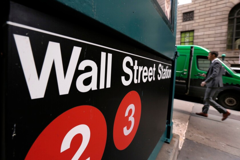 A man walks near a sign for the Wall Street subway station.