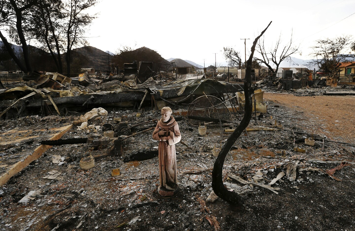 A religious icon stands in the charred remains of a neighborhood in South Lake.