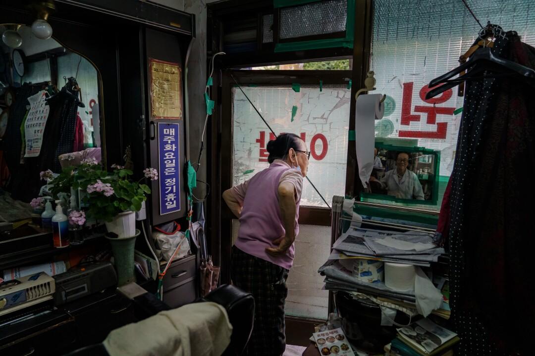 Lee Duk-hoon waits for customers at barbershop in Seoul.