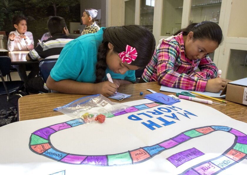 """Vista Magnet Middle School students Laisha Morales Montiel and Angelica Garcia Arellano work on their """"Math World"""" game."""