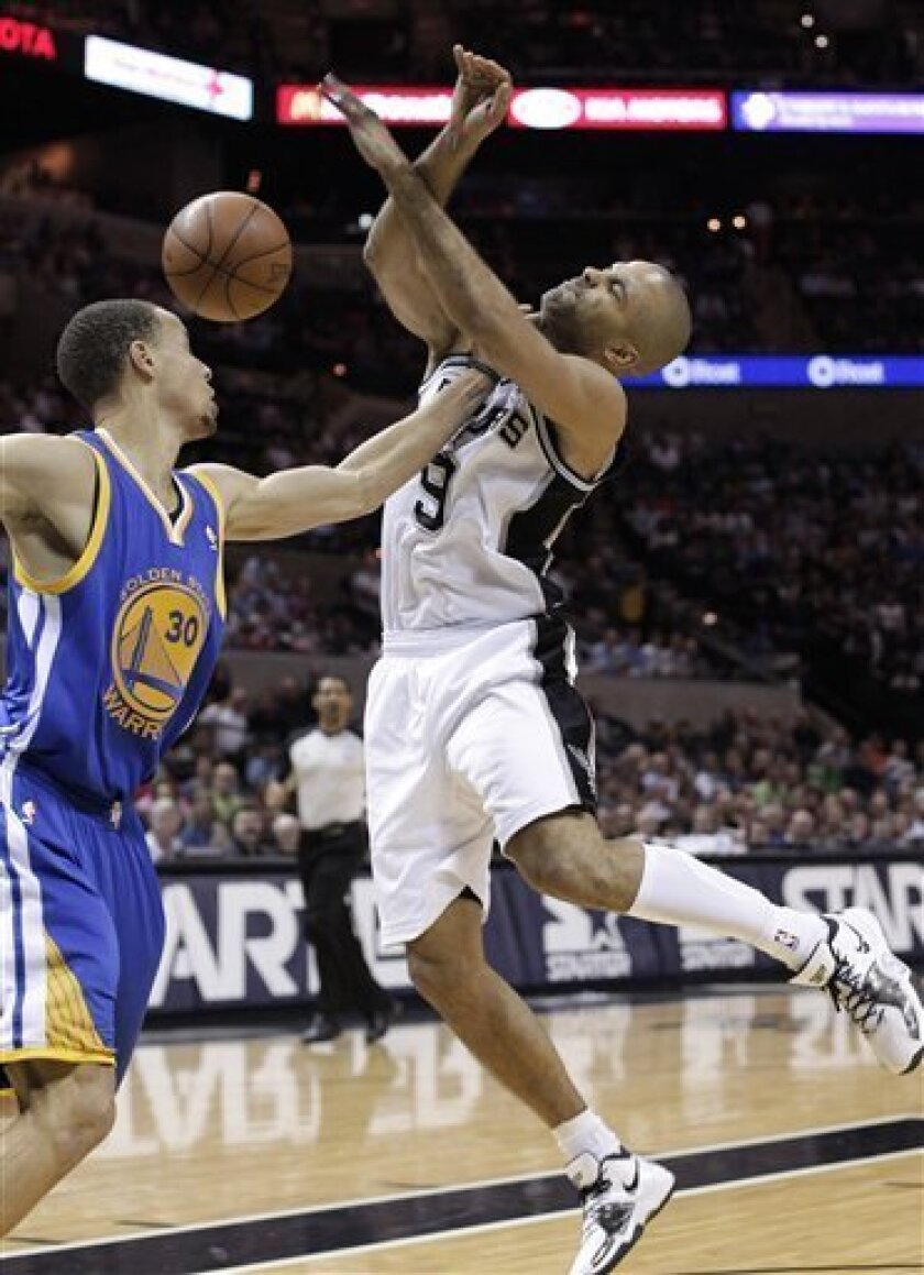 San Antonio Spurs' Tony Parker (9), of France, is fouled by Golden State Warriors' Stephen Curry (30) during the first quarter of an NBA basketball game, Monday, March 21, 2011, in San Antonio. (AP Photo/Eric Gay)