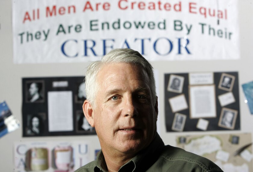 This file photo from 2010 shows Westview High School teacher Bradley Johnson in his classroom with one of the banners that a federal appeals court said he needed to remove. The U.S. Supreme Court has declined to review that decision. A Poway school district official said the banners are no longer i