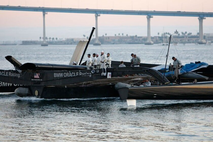 Crew members stand on one of the hulls as the mastless BMW Oracle trimaran is towed back into San Diego Bay at sunset after its mast broke during practice Tuesday, Nov. 3, 2009 in San Diego. The mast is valued at approximately $10,000,000. (AP Photo/Lenny Ignelzi)