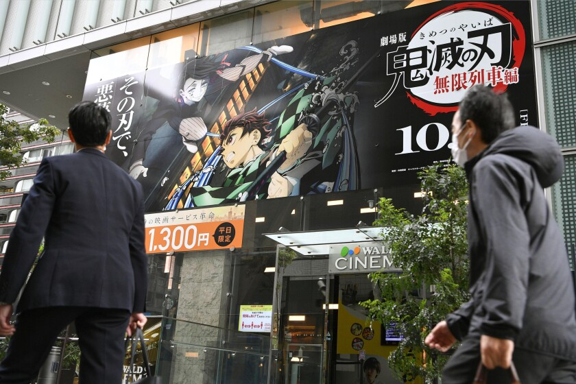 """People walk past a theater where the film """"Demon Slayer: Kimetsu no Yaiba the Movie: Mugen Train"""" is screened on its opening day, Oct. 16, 2020. """"Demon Slayer,"""" directed by Haruo Sotozaki, has become the biggest grossing film for Japan, including live-action films, and has struck a chord with pandemic-era Japan, and possibly with the world. (Tsuyoshi Ueda/Kyodo News via AP)"""