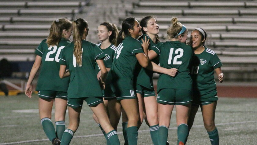 LCC senior Gracey Walke (third from right) celebrates with teammates after scoring.