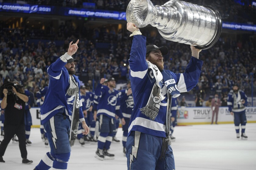 Tampa Bay Lightning center Brayden Point hoists the Stanley Cup after the team defeated the Montreal Canadiens in Game 5 of the NHL hockey Stanley Cup finals, Wednesday, July 7, 2021, in Tampa, Fla. (AP Photo/Phelan Ebenhack)