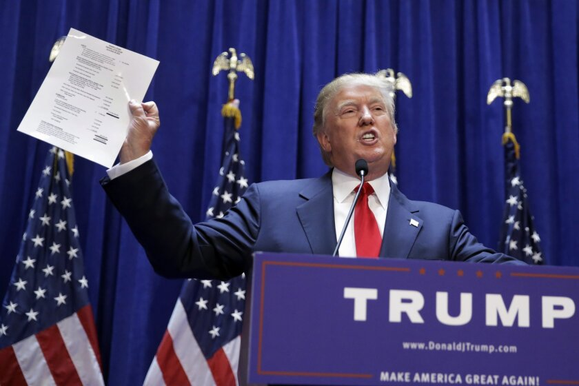 Donald Trump displays a document reportedly showing his net worth.