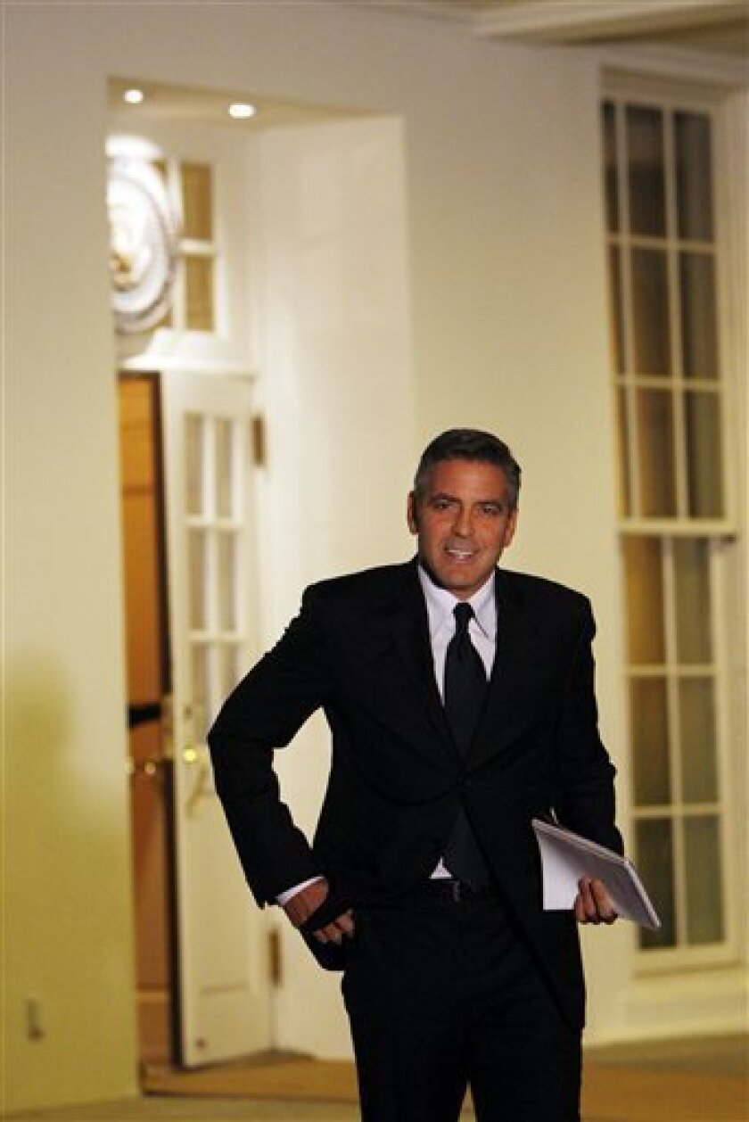 FILE - In this Feb. 23, 2009, file photo Actor George Clooney walks out of the West Wing of the White House in Washington following his meeting with President Barack Obama and Vice President Joe Biden. Celebrities Oprah Winfrey, Clooney, Denzel Washington and heavyweights from the financial services and high-tech industries were among those landing visits with President Barack Obama or others at the White House during his first months in office. (AP Photo/Pablo Martinez Monsivais, FILE)