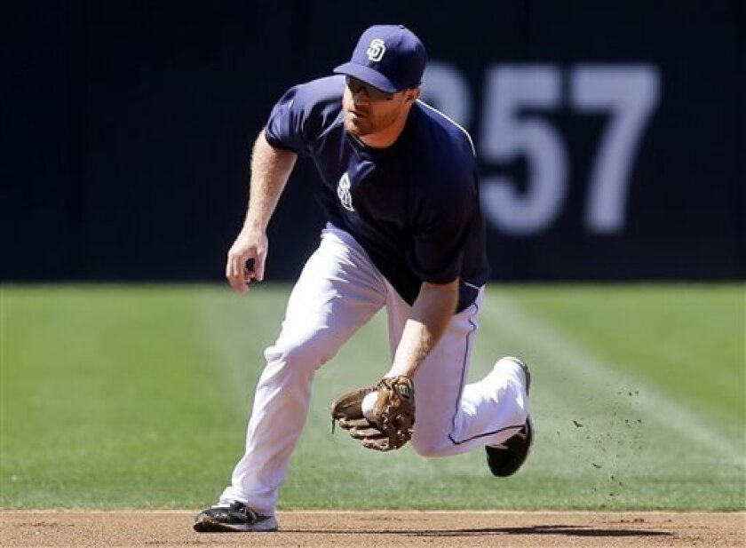 San Diego Padres utility player Logan Forsythe charges a ground ball during warmups for a baseball game against the Pittsburgh Pirates, Wednesday, Aug. 21, 2013, in San Diego. (AP Photo/Lenny Ignelzi)