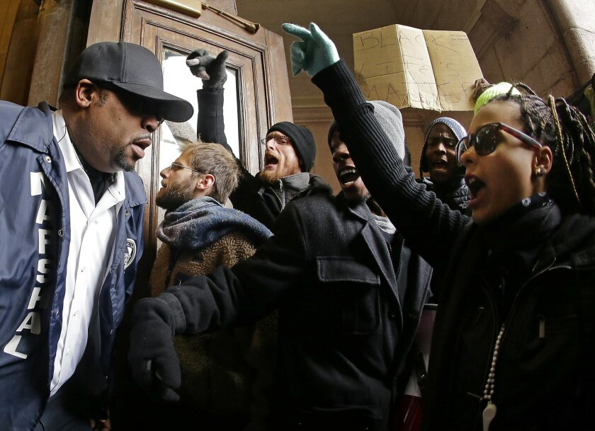Protesters confront a law enforcement officer as they try to enter City Hall Wednesday, Nov. 26, 2014, in St. Louis. Several people protesting the Ferguson grand jury decision stormed into City Hall in St. Louis on Wednesday, leading police to lock down the building and to call in more than a hundr