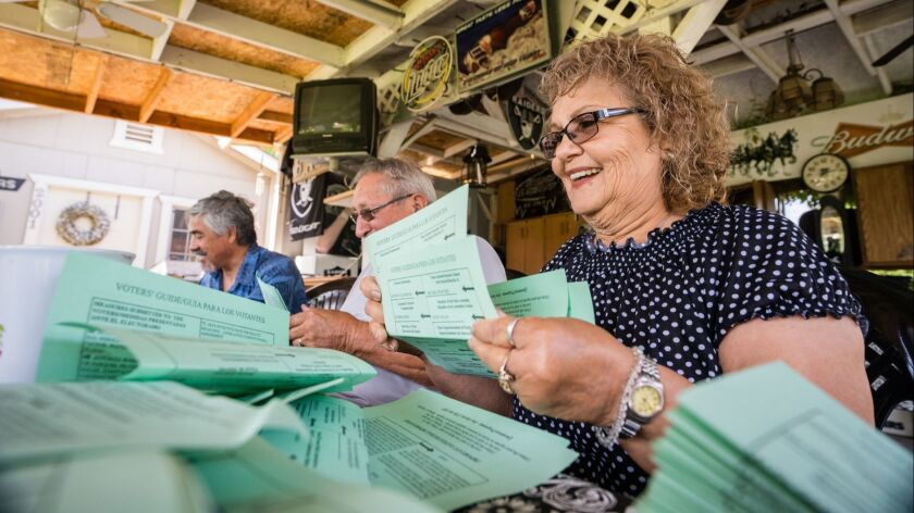 Mary Gonzales-Gomez, Raul Gomez, and Jose Ojeda and other members of the Latino Community Roundtable fold Democratic voter guides for passing out to homes in Corcoran, Calif. on May 20.