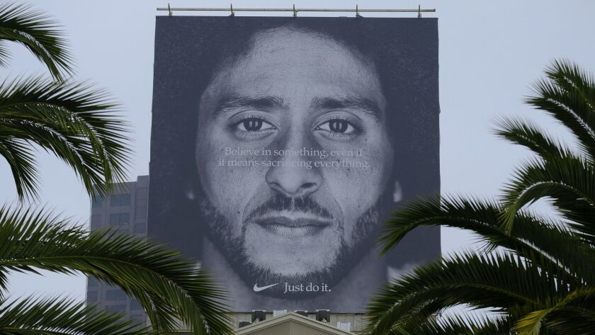 FILE- In this Sept. 5, 2018, file photo palm trees frame a large billboard on top of a Nike store th