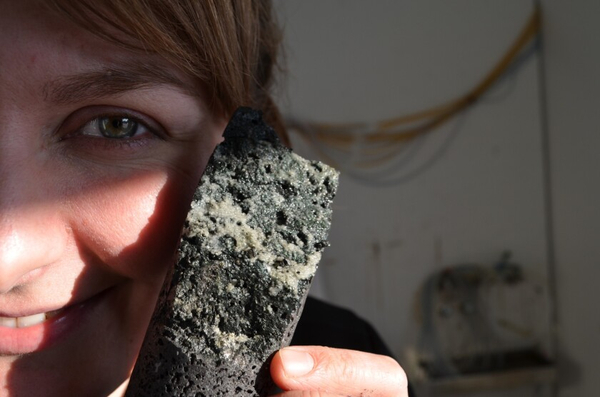 University of Iceland geologist Sandra Snaebjornsdottir holds up a core of porous basalt laced with carbonate minerals, evidence the carbon dioxide injection worked.