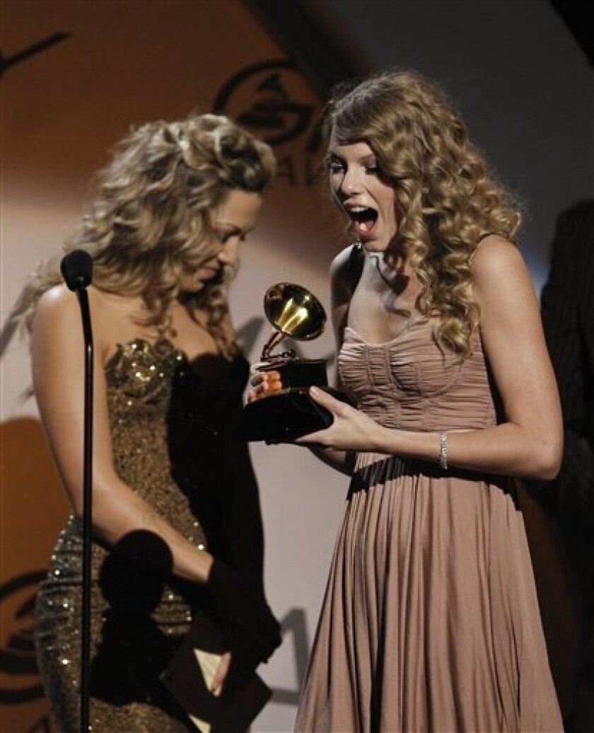 "Taylor Swift, right, accepts the best female country vocal performance award for ""White Horse"" at the Grammy Awards on Sunday, Jan. 31, 2010, in Los Angeles. (AP Photo/Matt Sayles)"