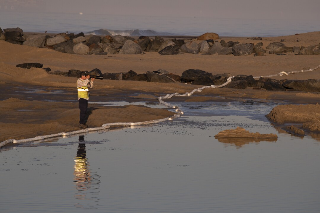 A man photographs the scene near a containment boom placed to trap oil at border of Huntington Beach and Newport Beach