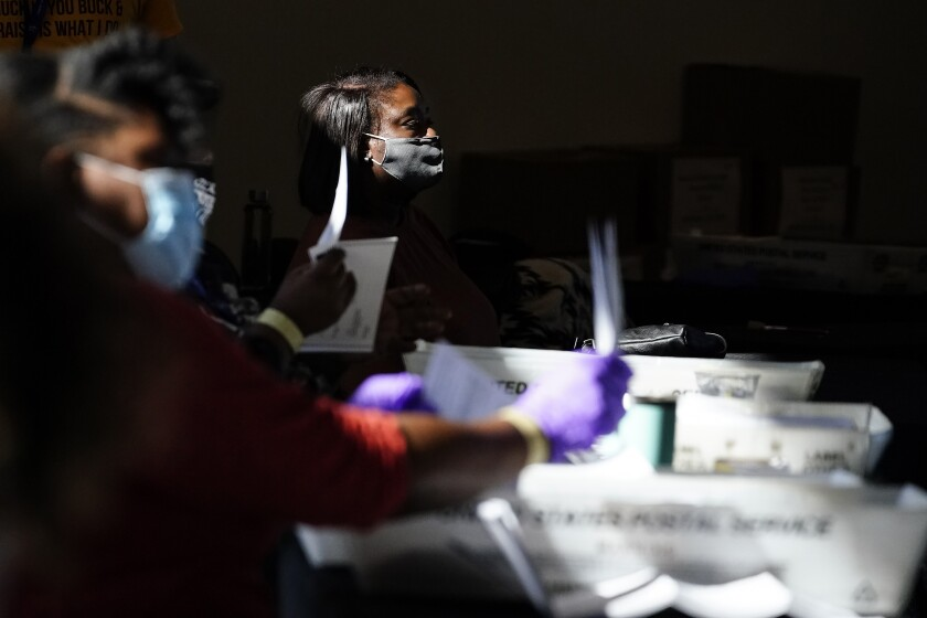Election personnel examines a ballot as vote counting in the general election continues at State Farm Arena, Wednesday, Nov. 4, 2020, in Atlanta. (AP Photo/Brynn Anderson)