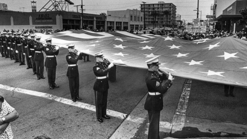 """En 1980, miembros de las fuerzas armadas y veteranos despliegan una bandera estadounidense de 42 x 75 pies en las calles, fuera del hogar de Thomas """"Ski"""" Demski, en Long Beach (Los Angeles Times)."""