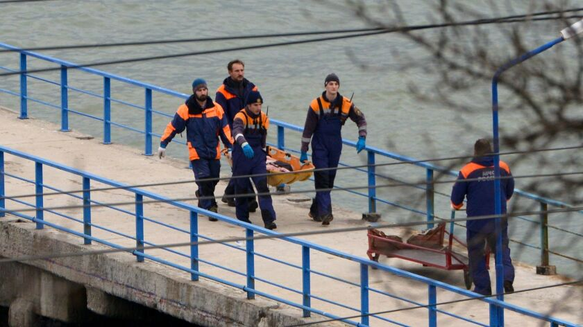 Russian rescue workers carry a body from the wreckage of the crashed plane, at a pier just outside Sochi, Russia, on Dec. 25, 2016.