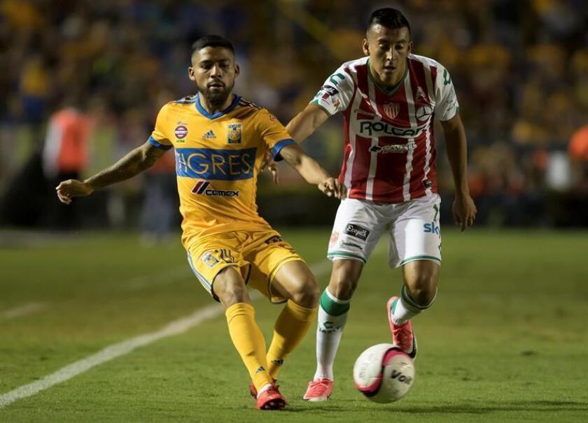 Javier Aquino (i) de Tigres disputa el balón con Daniel Álvarez (d) de Rayos de Necaxa. EFE/Archivo