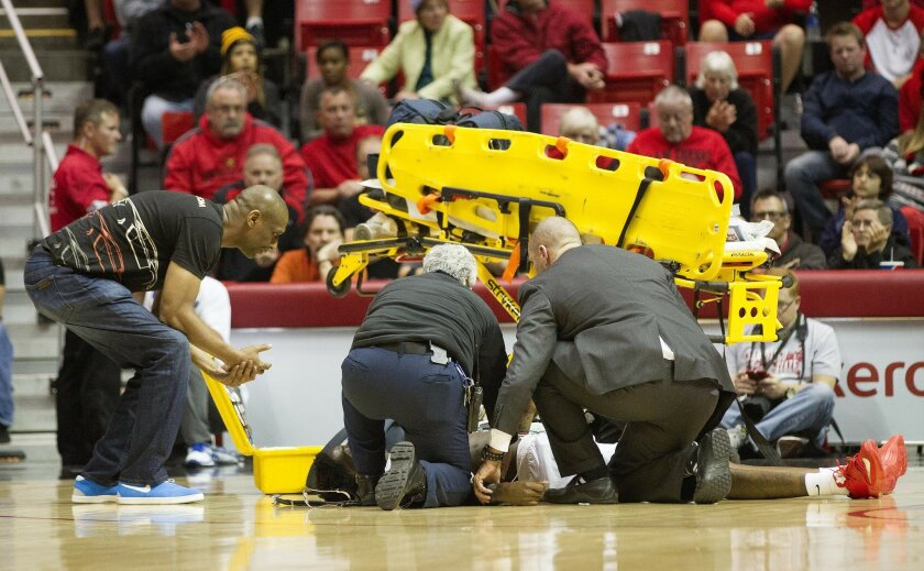 San Diego State vs. UC Riverside Mens Basketball at Viejas Arena on the campus of San Diego State. San Diego State Aztecs forward Dwayne Polee II (5) collapses and hits the floor during first half action against UC Riverside. He is seen being attended to by health staff as his father Dwayne Sr.